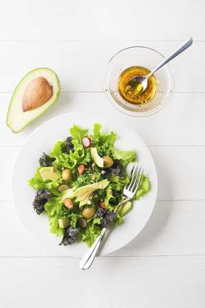 Fresh mixed green salad with avocado on white plate overhead shoot
