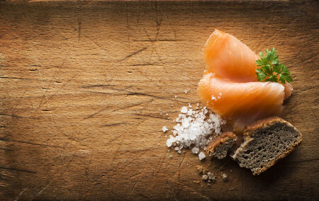 Slice of smoked salmon with sea salt and bread on wooden background photo