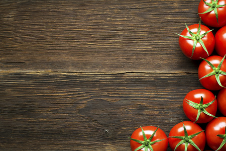 tomatoes: Fresh cherry tomatoes on rustic wooden background