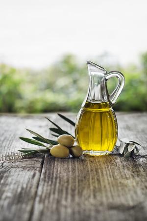 hoja de olivo: Aceite de oliva y la rama de olivo en la mesa de madera