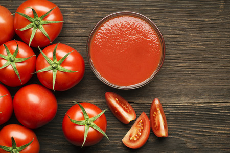 Fresh cherry tomato sauce on rustic wooden background Standard-Bild