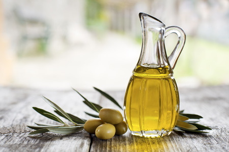 orchards: Olive oil and olive branch on the wooden table outside Stock Photo