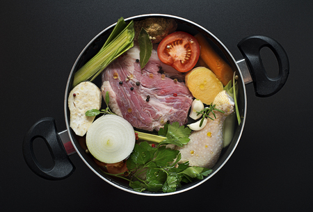 Fresh ingredients chicken and beef soup in a large pot photo