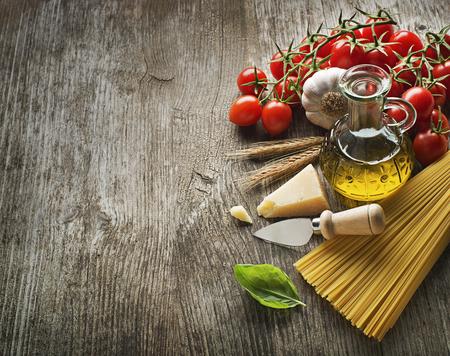 スパゲッティとヴィンテージの木製テーブルにパルメザン チーズとトマト