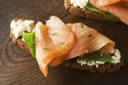 Slice of smoked salmon with bread on wooden background photo