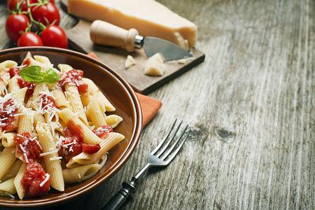 トマト ソースとパルメザン チーズのペンネ パスタのプレート 写真素材