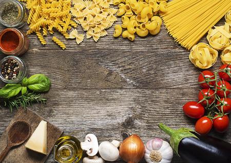 cooking: Pasta cruda con los ingredientes en el fondo de madera