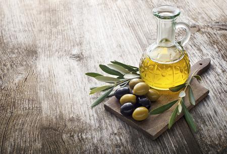 aceite oliva: Aceite de oliva y la rama de olivo en la mesa de madera