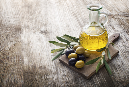 green glass bottle: Olive oil and olive branch on the wooden table
