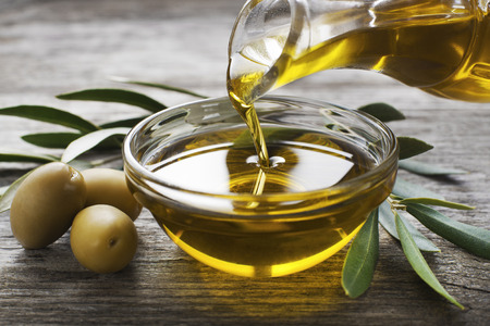 Bottle pouring virgin olive oil in a bowl close up Stock Photo