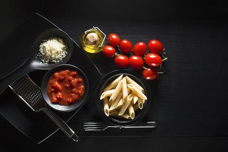 pastas: Penne pasta con salsa de tomate y queso parmesano sobre fondo negro Foto de archivo