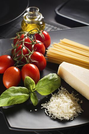 carte: Spaghetti and tomatoes with parmesan cheese on a black background