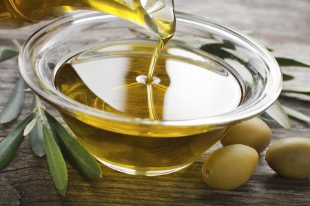 Botella que vierte el aceite de oliva virgen en un tazón de cerca