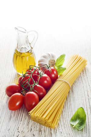 Spaghetti and tomatoes with oil on a vintage wooden table photo