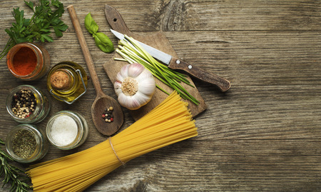 Pasta with spices and ingredients on old wooden table photo