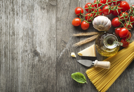 knife tomato: Spaghetti and tomatoes with parmesan cheese on a vintage wooden table Stock Photo