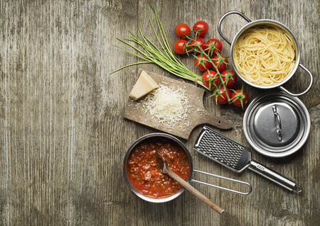cooking ingredients: Pasta with bolognese sauce and parmesan cheese on wooden table