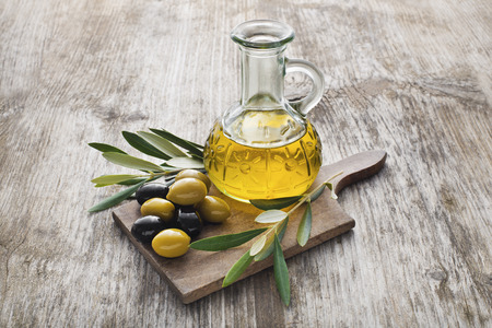 oilcan: Olive oil and olive branch on the wooden table