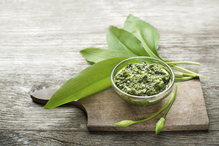 Wild garlic pesto on wood table close up
