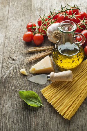 Spaghetti and tomatoes with parmesan cheese on a vintage wooden table photo