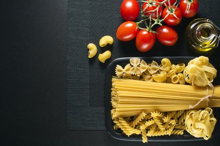 vegetarian food: Raw mixed pasta on black background overhead shoot Stock Photo