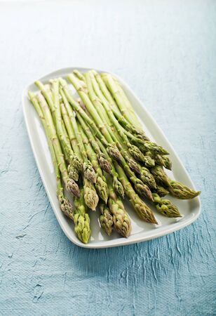 bunch up: Bunch of fresh asparagus on a plate close up