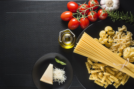 Pasta collection and fresh ingredients on a black background overhead shoot
