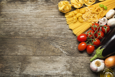 Pasta collection with fresh ingredients on wooden background photo
