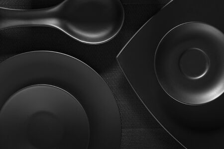 Top view of black empty plates on dark grey background