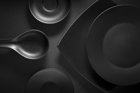 beautiful background: Top view of black empty plates on dark grey background.