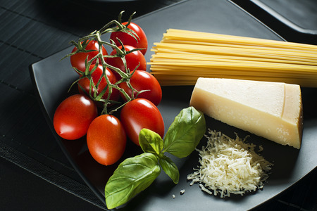 pasta sauce: Spaghetti and tomatoes with parmesan cheese on a black table. Stock Photo