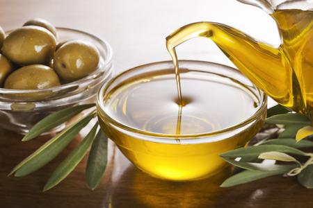 Fles gieten olijfolie in een kom close-up. Stockfoto