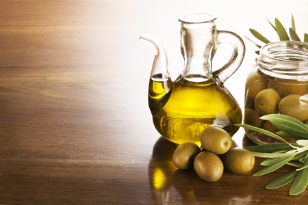 Olive oil and olives on a wooden table. Stockfoto
