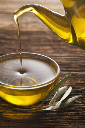 Bottle pouring virgin olive oil in a bowl close up. Stock Photo
