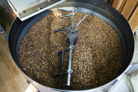 jamoke: Freshly roasted coffee beans falling into a spinning cooler professional machine. Stock Photo