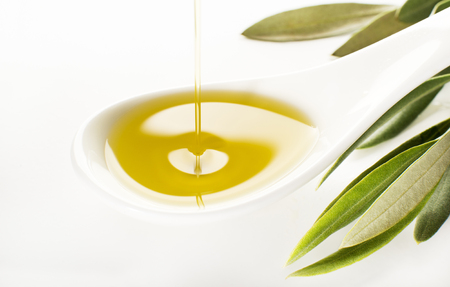 cuchara: Aceite de oliva virgen que vierte en la cuchara blanca. Foto de archivo
