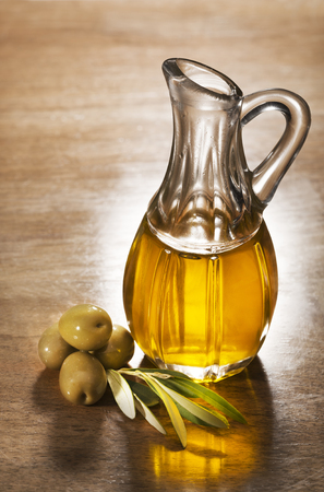 Olive oil and olive branch on the wooden table. Stockfoto