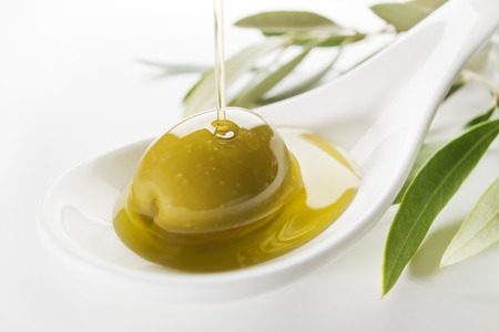 Virgin olive oil pouring on white spoon. Banque d'images