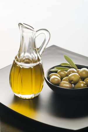 maturation: Olive oil and olives on a black plate.