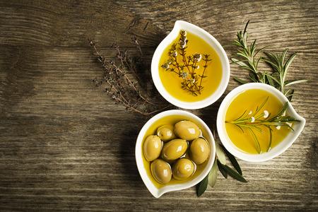 aceite de oliva: El aceite de oliva con las hierbas frescas en el fondo de madera. Foto de archivo