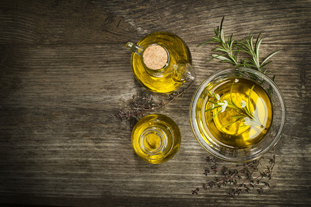 extra virgin olive oil: Olive oil with fresh herbs on wooden background.