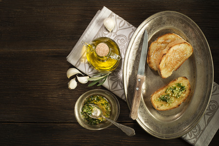 Toasted bread with garlic, herbs and olive oil on wooden background.