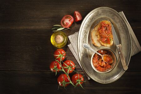 tomato sauce: Toasted bread with tomato and olive oil on wooden background.