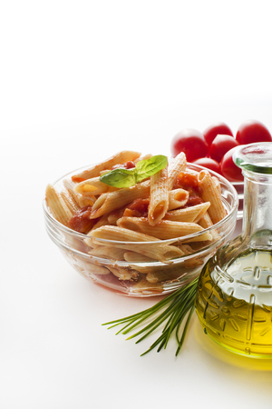 cooking oil: Penne pasta in tomato sauce decorated with basil on a white background.