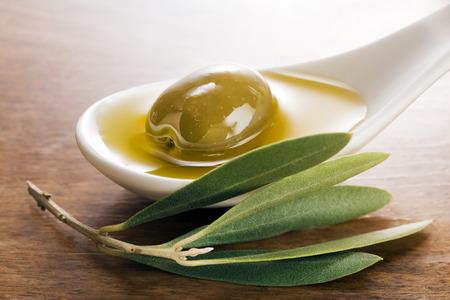 foglie ulivo: Olio vergine di oliva e frutta di oliva su un cucchiaio bianco vicino.