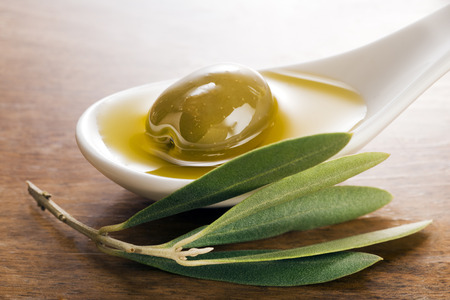 Virgin olive oil and olive fruit on white spoon close up.