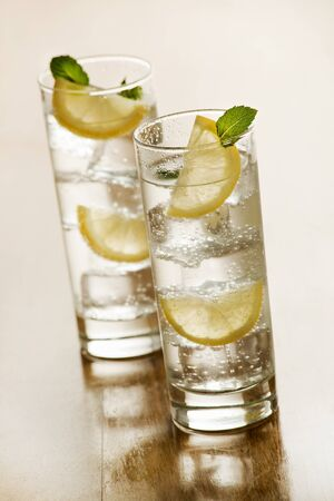 seltzer: Two glasses of Fresh Mineral water with ice and lemon.