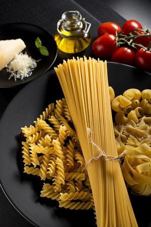 pasta: Pasta mezclada cruda con ingredientes sobre fondo negro. Foto de archivo