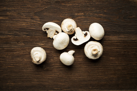 edible mushroom: Fresh mushrooms champignons on a wooden background.
