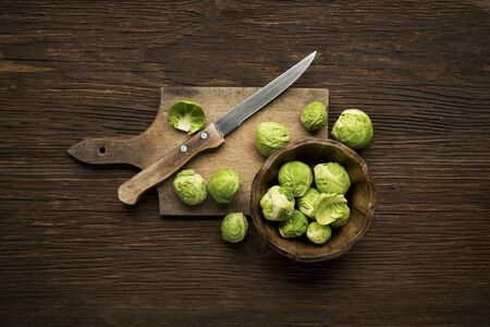 sprouts: Fresh raw Brussels sprouts on a wooden background. Stock Photo
